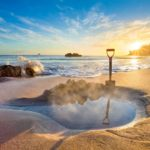 A beautiful beach at sunset with a steaming waterhole and a shuffle in the center